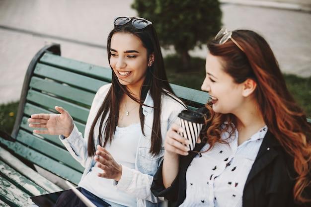Belle jeune brune expliquant quelque chose en gesticulant à sa petite amie pendant qu'une autre la regarde en train de boire du café assise sur un banc.