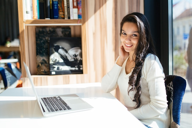 Belle jeune brune mignonne à l'aide d'un ordinateur portable au café