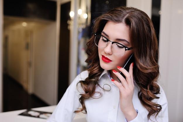 Belle jeune brune portant des lunettes parlant sur téléphone portable