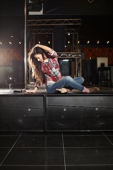 Belle jeune chanteuse pop star souriante avec microphone assis sur la scène dans le club