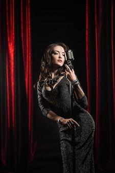 Belle jeune chanteuse en robe noire posant avec microphone