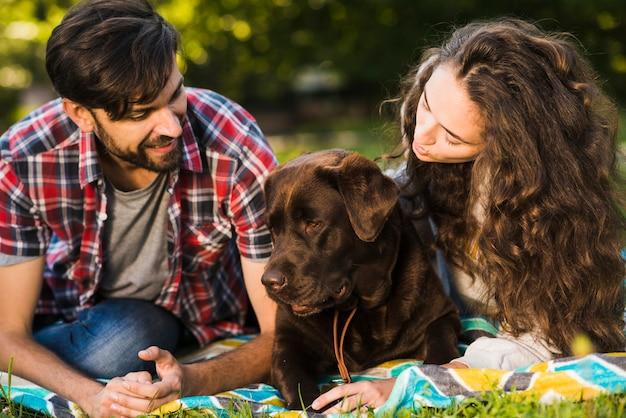 Belle jeune couple avec leur chien dans jardin