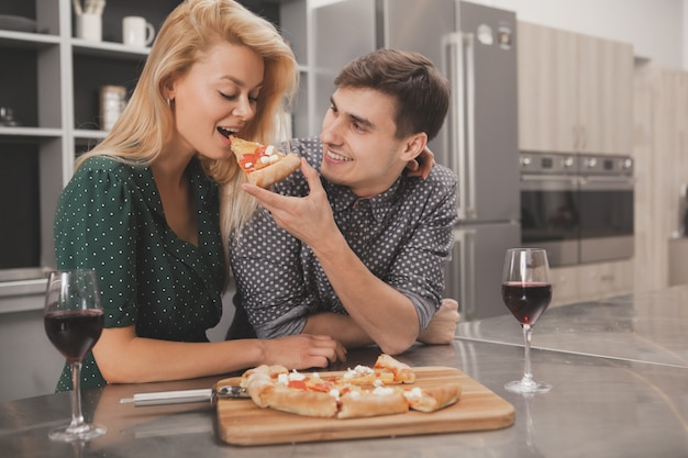 Belle jeune couple mangeant une pizza ensemble à la cuisine