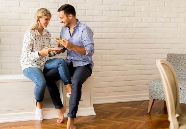Belle jeune couple en train de manger une pizza