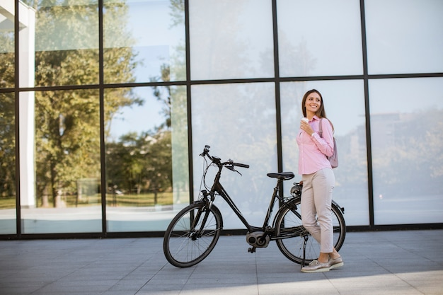Belle jeune cycliste boit du café chaud dans une tasse de vélo électrique en milieu urbain
