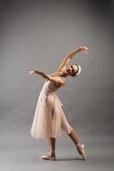 Belle jeune danseuse de ballet en maillot de bain beige posant sur des pointes sur fond de studio gris clair