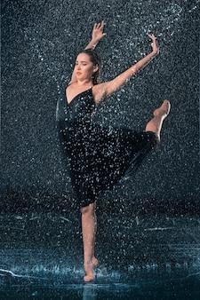 La belle jeune danseuse moderne dansant sous les gouttes d'eau