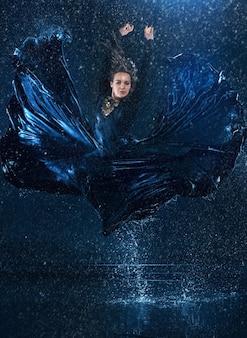 La belle jeune danseuse moderne danse sous des gouttes d'eau