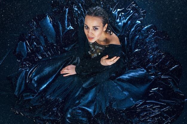 La belle jeune danseuse moderne posant sous des gouttes d'eau