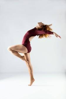 Belle jeune danseuse professionnelle dansant sur fond blanc.
