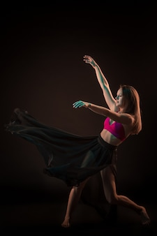 Belle jeune danseuse en robe beige dansant sur fond noir