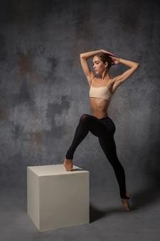 Belle jeune danseuse de style moderne posant sur un cube blanc sur un fond gris studio