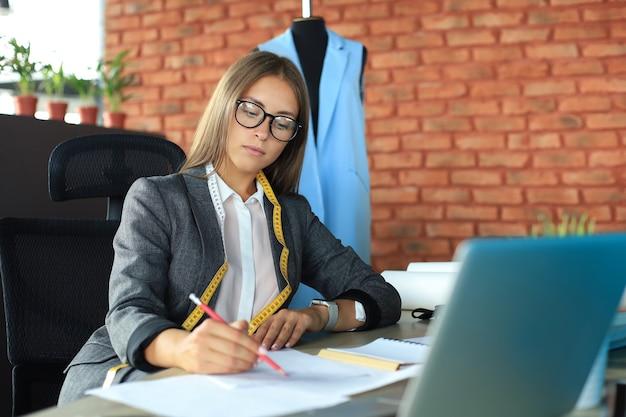 Belle jeune designer prenant des notes alors qu'elle était assise dans son studio.