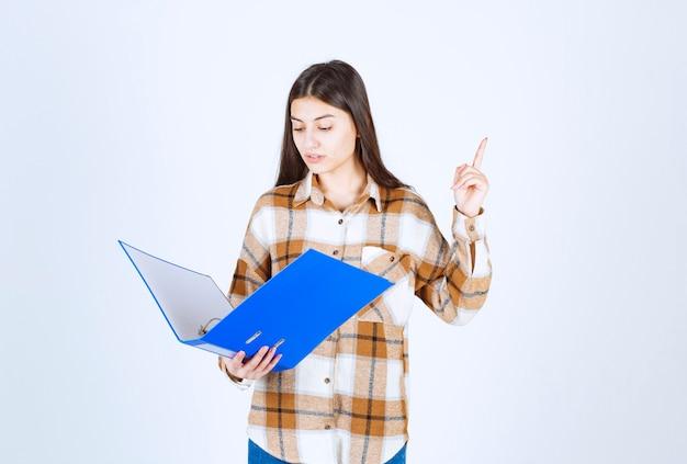 Belle jeune employée regardant des documents à l'intérieur du dossier bleu.