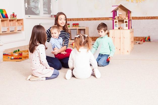 Belle jeune enseignante montrant des enfants d'âge préscolaire à la lettre, les enfants s'assoient en cercle
