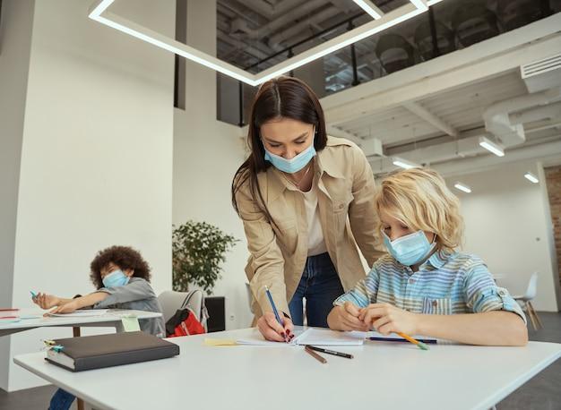 Belle jeune enseignante portant un masque protecteur aidant le petit garçon avec la tâche des enfants