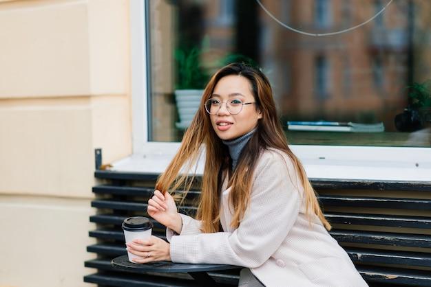 Belle jeune étudiante chinoise tenant une tasse de café dans la rue