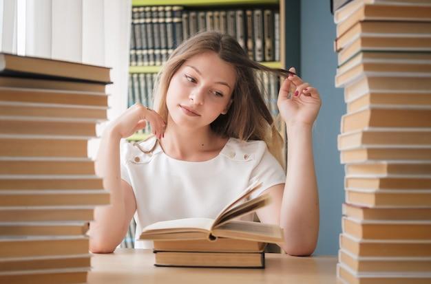 Une belle jeune étudiante est assise dans la bibliothèque parmi d'énormes piles de livres