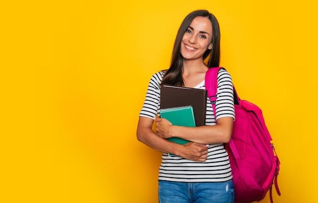 Belle jeune étudiante souriante avec des livres et un sac à dos pose et regarde la caméra