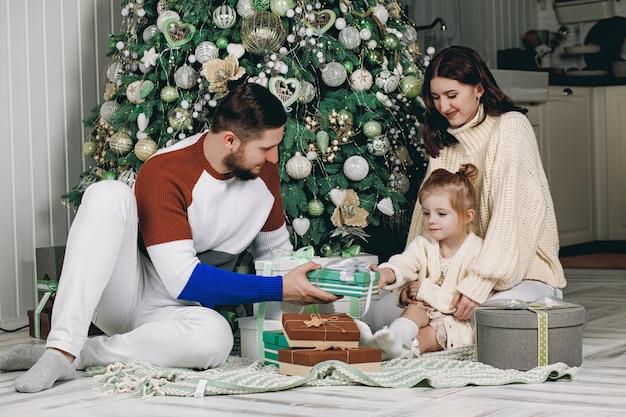 Belle jeune famille assise à côté d'un arbre de noël joliment décoré