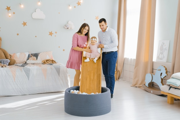 Belle jeune famille caucasienne jouant avec leur fille d'un an dans la chambre des enfants. la fille glisse sur le toboggan dans la piscine avec des balles