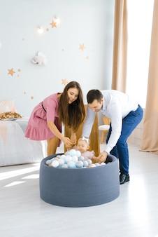 Belle jeune famille caucasienne jouant avec leur fille d'un an dans la chambre des enfants.