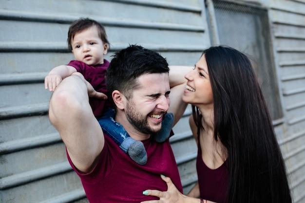 Belle jeune famille avec enfant posant sur mur gris