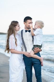 Belle jeune famille, le pape tient son fils dans ses bras. concept d'enfance et de parentalité heureux.