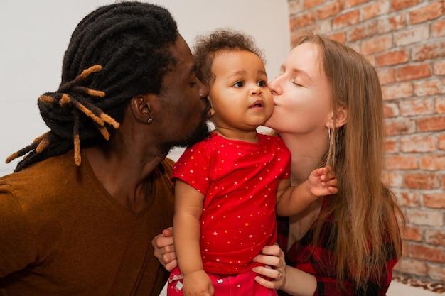 Belle jeune famille avec petite fille à la maison