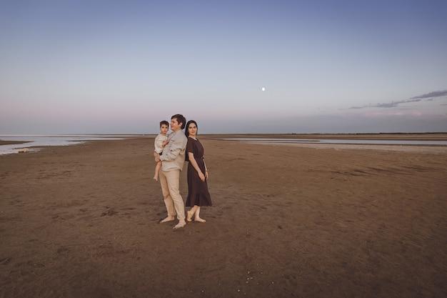 Belle jeune famille sur la plage du soir. aspect familial des vêtements en lin naturel. espace de copie.