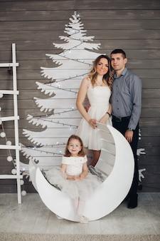 Belle jeune famille posant par arbre de noël peint.