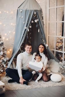 Belle jeune famille sous baldaquin. décorations de noël.