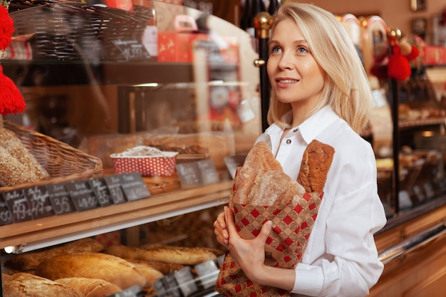 Belle jeune femme achetant un délicieux pain frais à la boulangerie, copiez l'espace