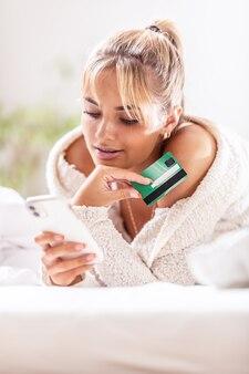 Belle jeune femme achète en ligne via le commerce électronique tenant une carte de paiement dans l'autre main.