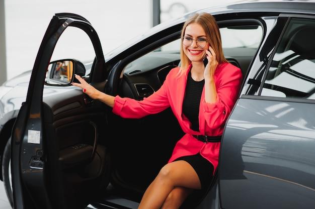 Belle jeune femme achète une voiture dans la salle du concessionnaire