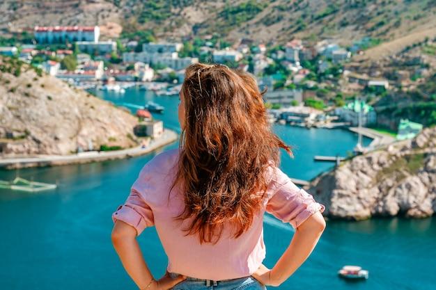Une belle jeune femme admire le paysage pittoresque avec vue sur balaclava avec yacht