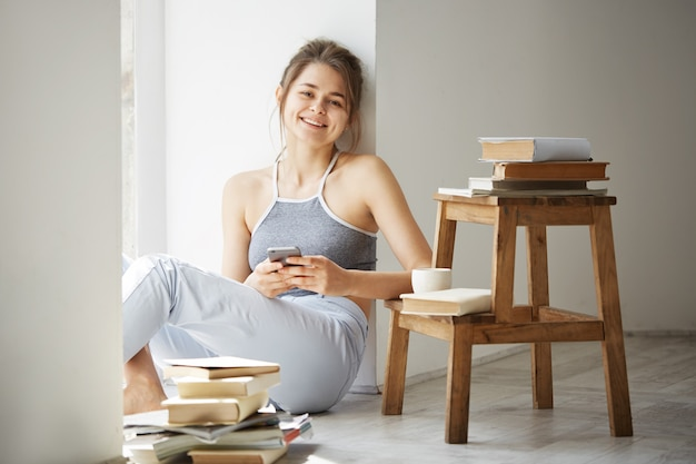 Belle jeune femme adolescente surfer sur internet au téléphone souriant assis sur le sol parmi les vieux livres près de fenêtre sur mur blanc.