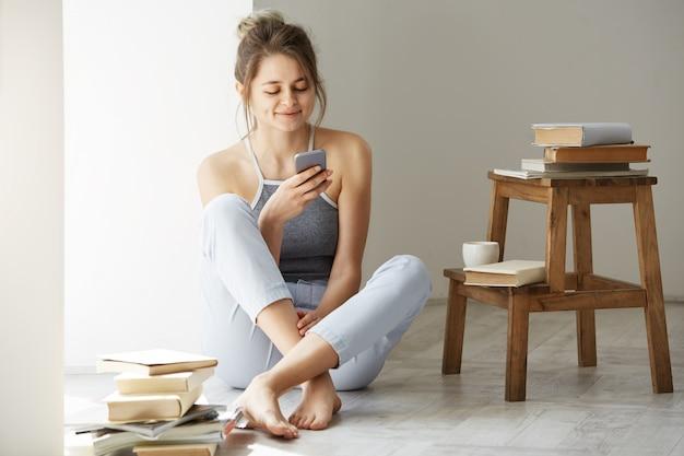 Belle jeune femme adolescente surfer sur le web en regardant l'écran du téléphone souriant assis sur le sol parmi les vieux livres près de la fenêtre sur le mur blanc.