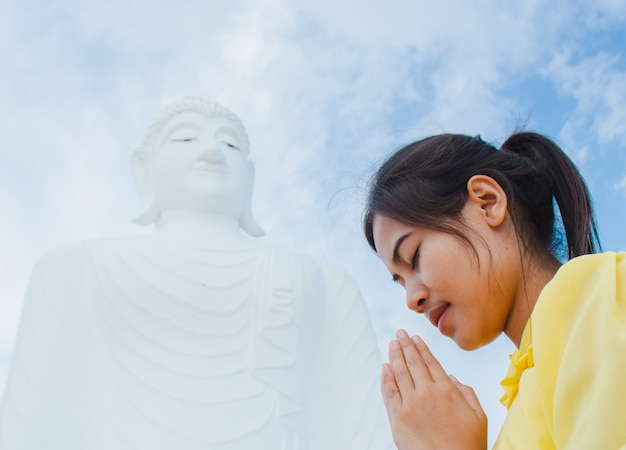 Belle jeune femme adore le bouddha.