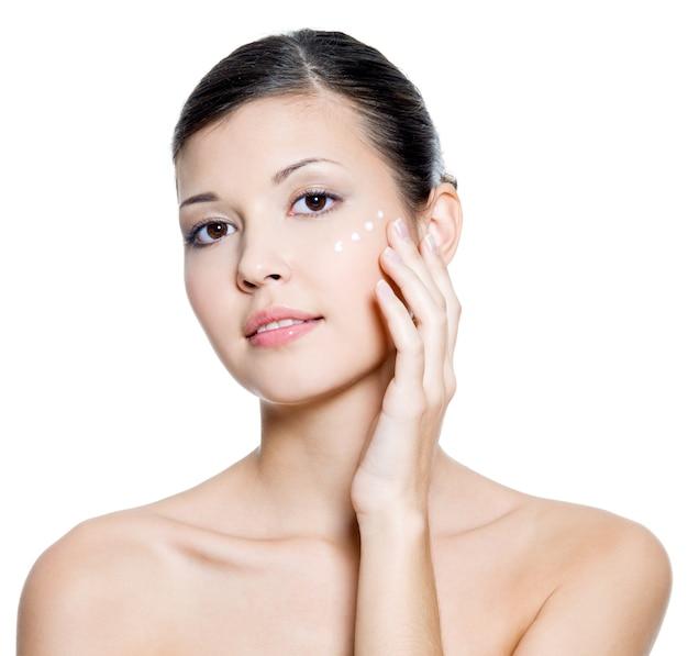 Belle jeune femme adulte appliquant une crème cosmétique autour de l'œil.