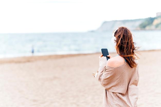 Belle jeune femme adulte écoutant de la musique sur la plage par un été nuageux ou une journée de printemps portant des écouteurs
