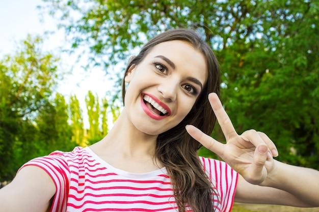 Belle jeune femme adulte prenant une photo d'elle-même