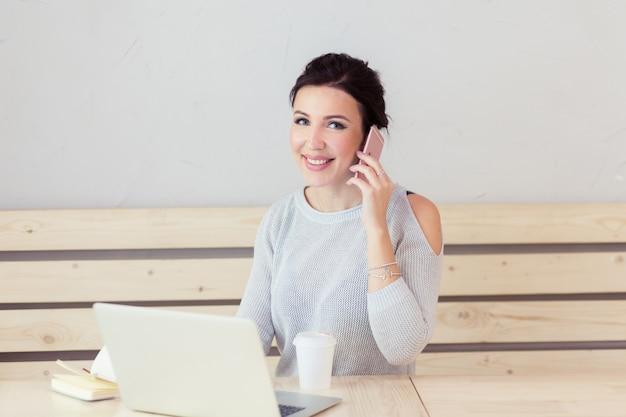 Belle jeune femme adulte avec téléphone portable tout en travaillant sur un ordinateur portable au bureau à côté d'une tasse de café