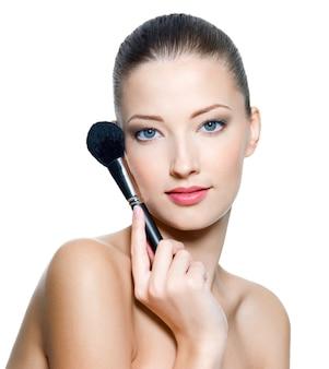 Belle jeune femme adulte tient la brosse de maquillage pour appliquer du rouge ou de la poudre. top model