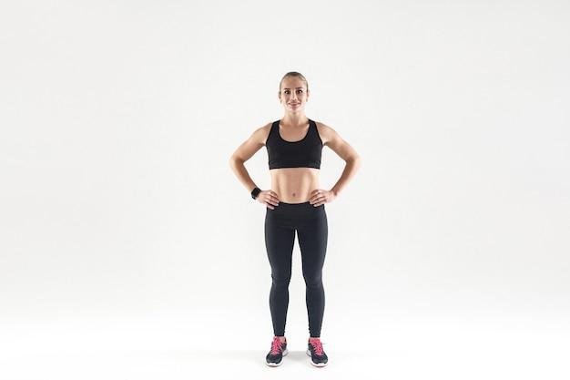Belle jeune femme adulte en vêtements de sport, regardant la caméra et souriant, debout sur un fond gris