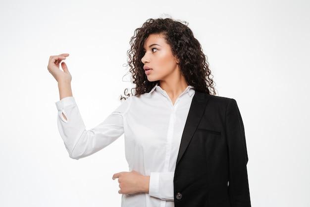 Belle jeune femme d'affaires africaine tenant quelque chose dans sa main