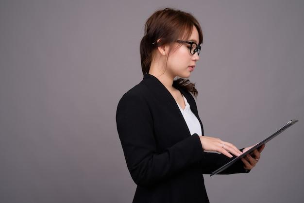 Belle jeune femme d'affaires asiatique contre le mur gris
