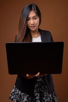 Belle jeune femme d'affaires asiatique sur fond marron