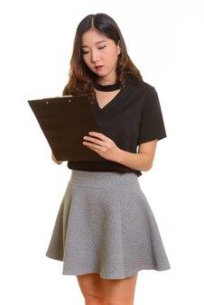 Belle jeune femme d'affaires asiatique rapport d'écriture isolé sur blanc