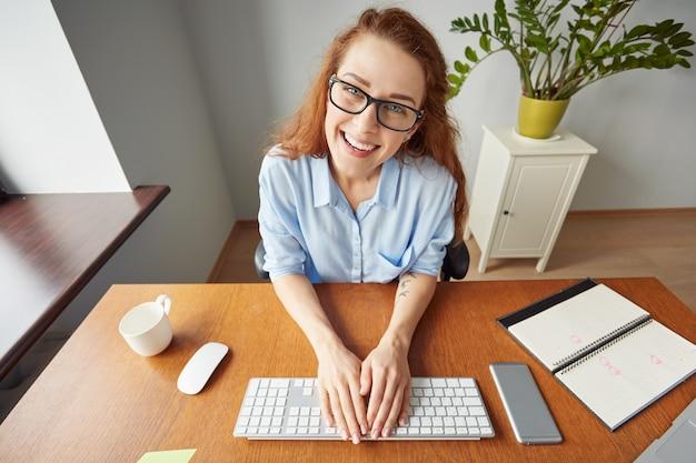 Belle jeune femme d'affaires assis devant l'écran de l'ordinateur